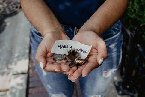 Girl holding change. Photo by Kat Yukawa via Unsplash.
